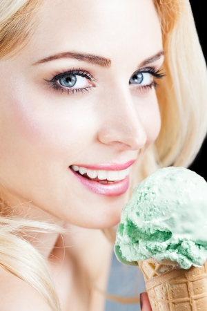 Attractive Blond Woman With Ice Cream, Looking At Camera  photo