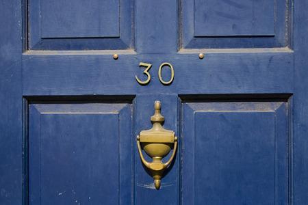 fachada de casa: Tradicional british residencial puerta con martinete