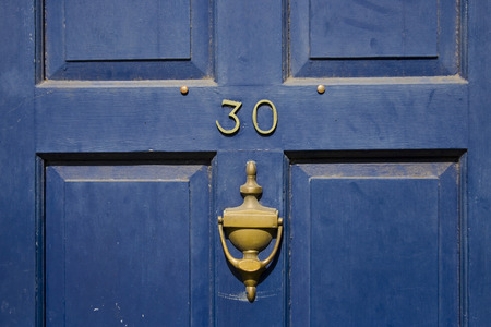 view of a wooden doorway: Traditional british residential front door with knocker