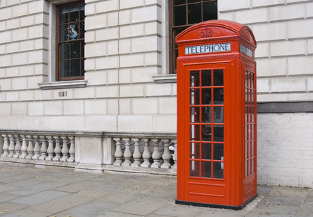 telephone booth: Classical single british red phone booth with wall background