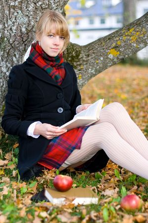 Young student girl is studying outside near the tree