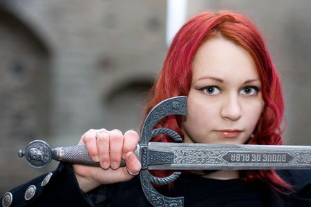 gripe: Redhead gothic girl with a ancient sword Stock Photo