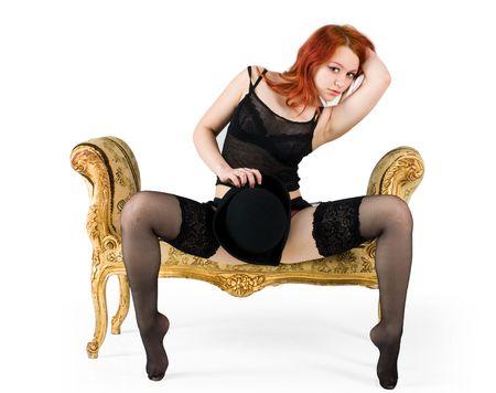 black stockings: Redhair girl in black stockings posing on a sofa Stock Photo