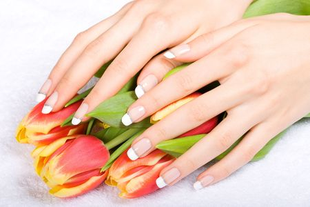 Woman hands with beautiful manicure holding fresh tulips Stock Photo