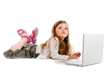 Adorable caucasian little girl lying with laptop photo