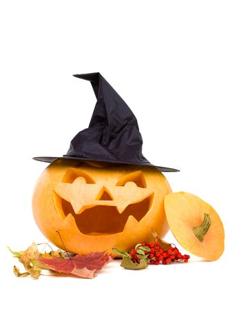 Halloween carved pumpkin with maple leafs and rowan berries photo