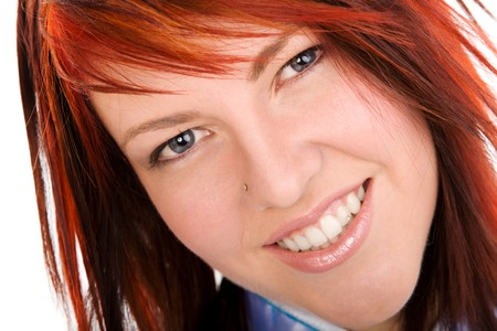 Closeup portrait of a young redhead woman on isolated white