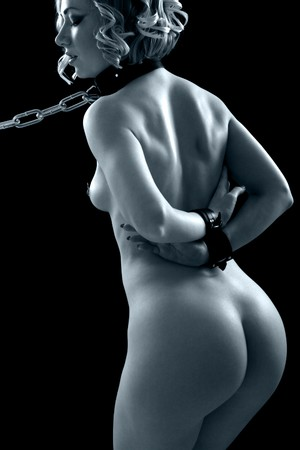 Nude young woman in bdsm accessories on black background Stock Photo
