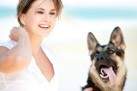Young woman enjoying a sunny summer day on a beach with her dog