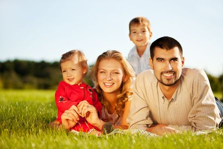 Happy family of 4 people lying ona grass under summer sun. Focus is on the man. photo