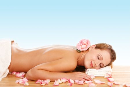 Young attractive woman lying and relaxing in spa center