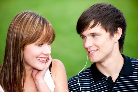 Young couple sharing a headphones while listening to a favorite  beat photo