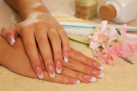 human fingernail: Hands of young woman with french manicure on the towel Stock Photo