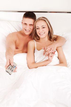 pareja viendo tv: Pareja joven feliz viendo whilem televisi�n acostado en una cama
