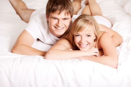 Young smiling couple in a bed on white sheets photo