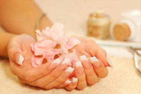Mains de la jeune femme avec manucure fran�ais sur la serviette Banque d'images