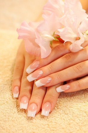 Hands of young woman with french manicure on the towel Stock Photo