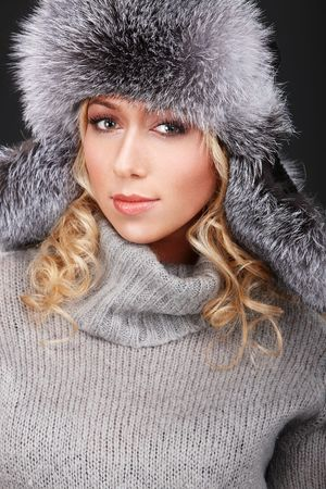 Portrait of young girl in fur hat and grey sweater photo