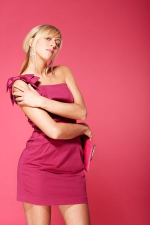 Young blond girl standing over pink background