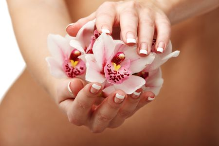 Closeup of young woman hands with magenta orchid over her slim body