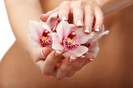 body slim: Gros plan des mains de la jeune femme avec une orchid�e magenta sur son corps mince