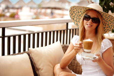 Attractive woman enjoying coffee on a vacation during summer day photo