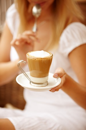 Atrractive woman enjpying coffee on a vacation during summer day. Focus is on the top of the cup. photo