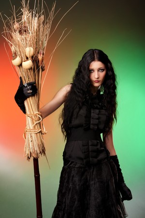 Halloween witch with a broom over color background Stock Photo - 7623090
