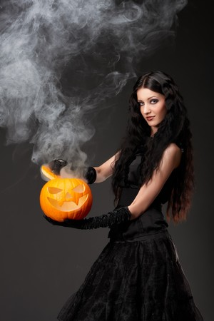 Halloween witch with a broom and smoke coming out of carved pumpkin photo