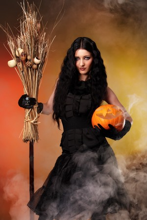 Halloween witch with a broom and carved pumpkin over color background with smoke Stock Photo