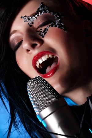 mouth closed: Closeup portrait of singing woman with closed eyes