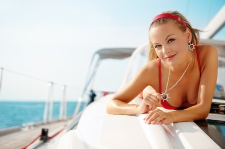 Attractive girl sailing on a yacht on summer day