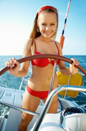 Attractive girl sailing on a yacht on summer day photo