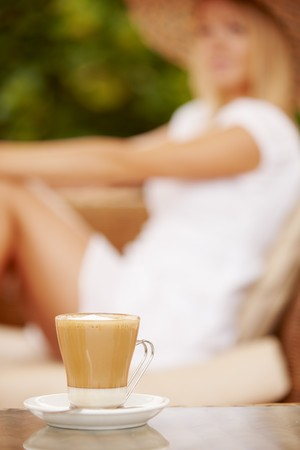 Attractive woman enjoying coffee on a vacation during summer day. Focus is on the cup photo
