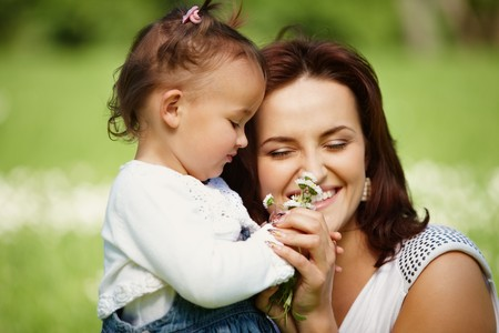 Young mother with child outside on a summer day. Focus is on the girl. Stock Photo - 7811631