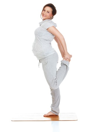 Pregnant woman doing gymnastic exercises on isolated white background Stock Photo