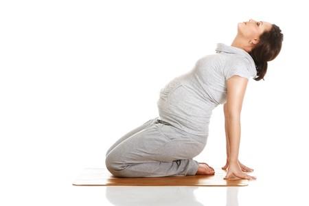 Femme enceinte, faire des exercices de gymnastiques sur fond blanc isol�e