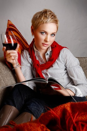 blue leather sofa: Portrait of young woman sitting on a coach and drinking red wine Stock Photo