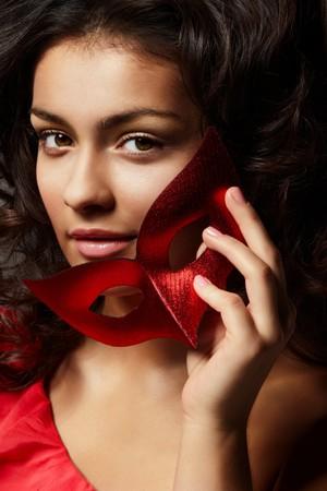Portrait de jeune femme belle avec masque rouge Carnaval