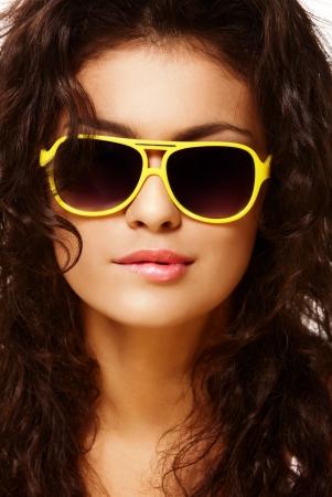 Fashion portrait of biting lip lady in yellow sunglasses