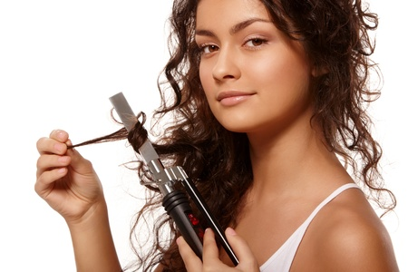 Beauty portrait with curling iron over isolated white background