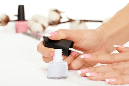 polisher: Hands of young woman holding nail polisher over white towel