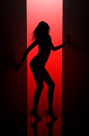 Silhouette of  dancing girl between black curtains