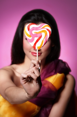 Portrait of a girl holding lollypop in front of her. Focus is on the lollypop. Stock Photo - 9341391