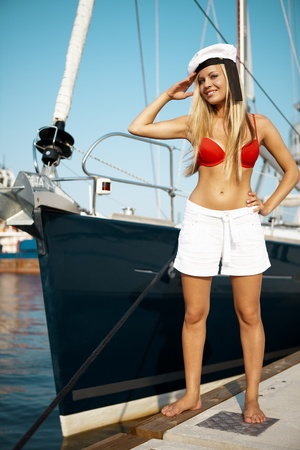 Beautiful girl posing with a yacht on sunny day photo