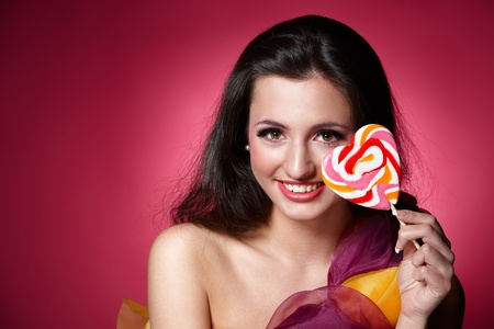Portrait of a girl holding lollypop over pink background Stock Photo - 9650835