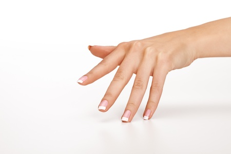 Female hand with french manicure touching seamless background