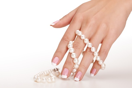 Hands holding pearls over seamless background