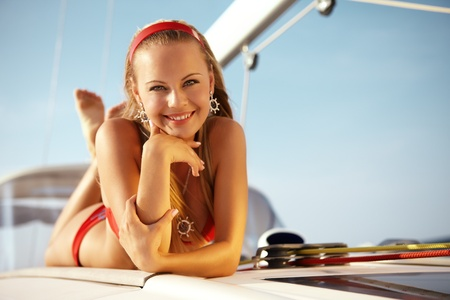 Beautiful girl posing with a yacht on sunny day Stock Photo - 9650868