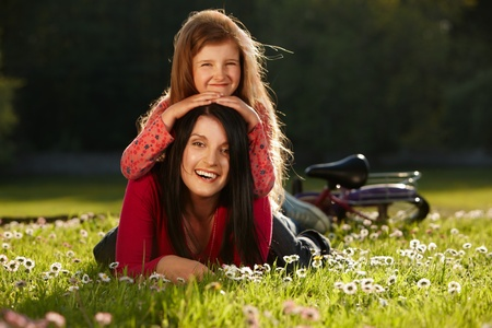 Mother and daughter enjoying summer day lying on a grass photo